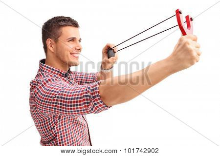Profile shot of a young cheerful man shooting a slingshot and smiling isolated on white background