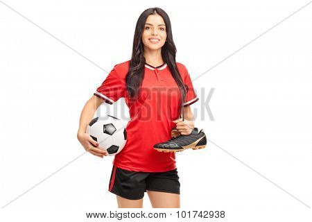 Young female soccer player holding a ball and carrying her soccer boots over her shoulder isolated on white background