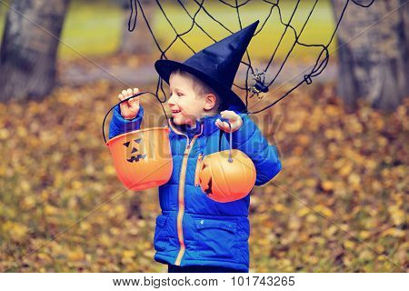 little boy in halloween costume at autumn park