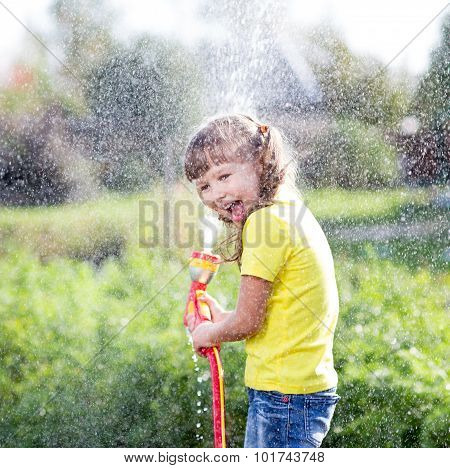 Cheerful kid watering plants from hose spray in garden at backyard of house at sunny summertime