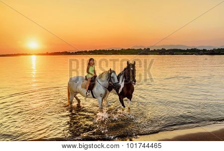 Beautiful Litlle Girl Riding Horse In  Sunset By The Sea On The Island Of Ada Bojana, Montenegro