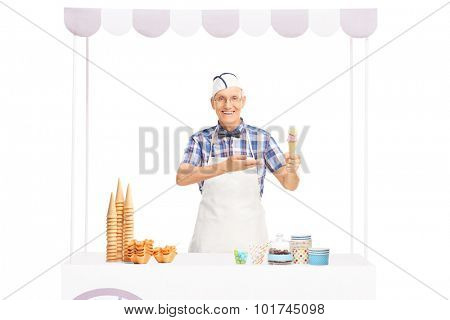 Mature ice cream seller holding an ice cream cone in one hand and pointing towards it with the other isolated on white background