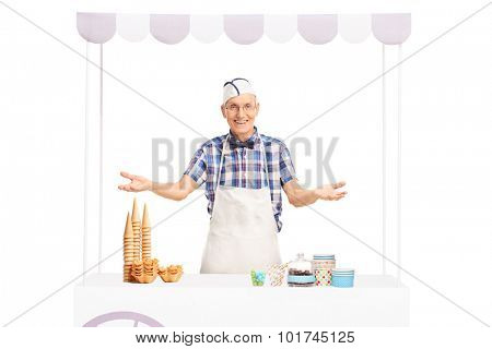 Studio shot of a mature ice cream seller standing behind a stall and making a welcoming gesture isolated on white background