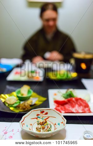 Traditional Japanese dinner of Nagano region with a variety of food. Woman on background wearing yukata kimono.