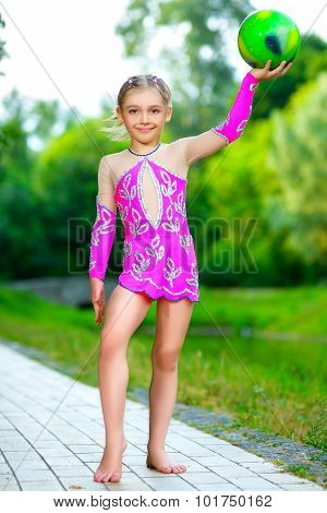 outdoor portrait of young cute little girl gymnast training with ball
