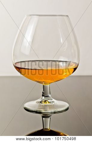 Snifter Of Brandy In Elegant Typical Cognac Glass On White Light Background