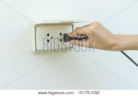 Female Hand Plugging In Appliance To Electrical Outlet In Wall Outdoor