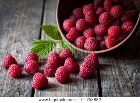 Fresh organic healthy raspberry with mint leaves in clay dish on vintage wooden table background