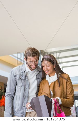 Young happy couple looking at shopping bags inside of a shopping mall