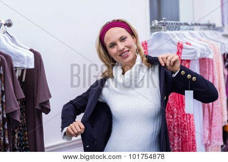 Portrait of smiling woman putting on blue coat in clothing store