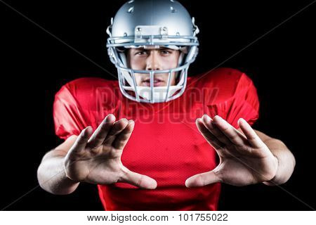 Portrait of sportsman defending while playing American football against black background