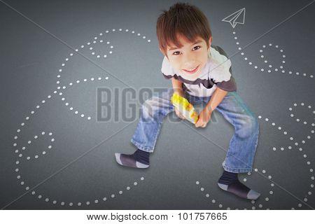 Cute boy sitting with building blocks against grey