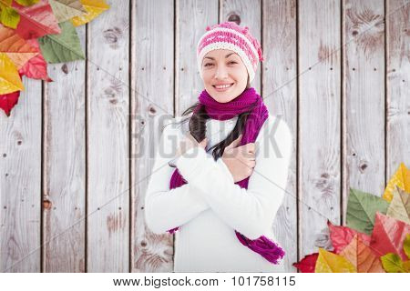 Attractive woman wearing a warm het against autumn leaves on wood