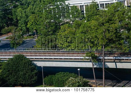 Rapid Transit Rail Line By Trees And Building