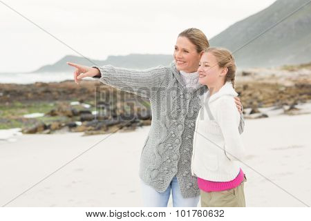 Mother and daughter looing towards the sea together