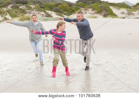 Parents chasing their kid for fun at the beach
