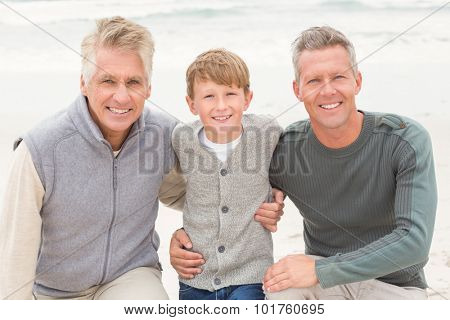 Young boy with his father and grandfather at the beach