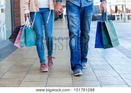 Couple with shopping bags holding hands at shopping mall