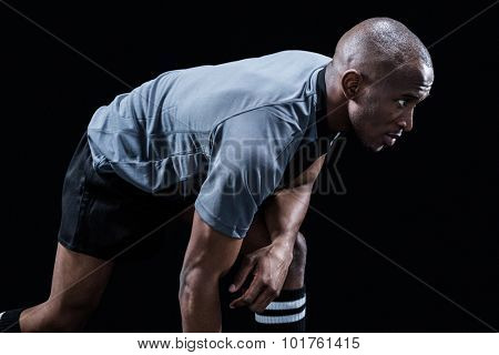 Determined sportsman bending while playing rugby against black background
