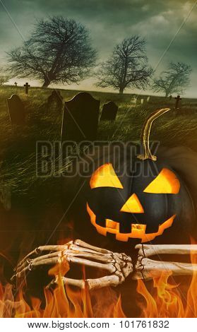 Black pumpkin with skeleton hand with graveyard in background