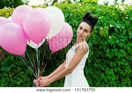 beautiful woman with balloons on a background of green hedgerow