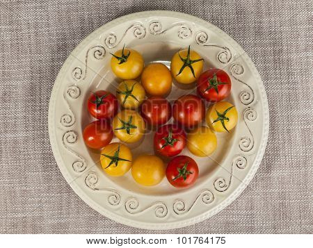 Fresh red and yellow cherry tomatoes on a porcelain plate in a rustic style.