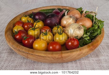 Fresh red and yellow cherry tomatoes and cucumbers, onions on a wooden tray in a rustic style. Good ingredients for the salad, cucumbers, tomatoes, onions and green salad mix.