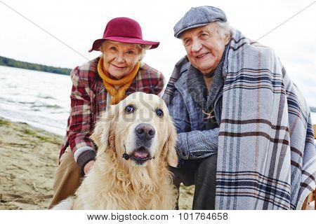 Retired couple and their pet relaxing by seaside on weekend