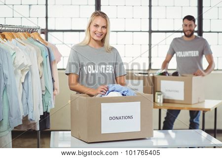Volunteer separating clothes from donation box with man in backkground