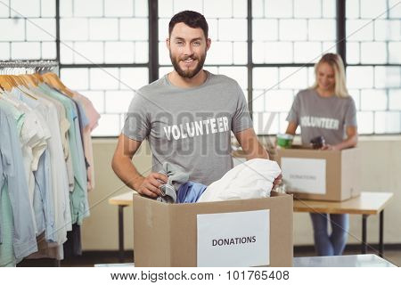 Portrait of smiling volunteer separating clothes from donation box in creative office