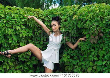 expressive emotional woman near green hedgerow
