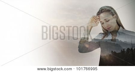 Upset woman touching forehead against trees and mountain range against cloudy sky