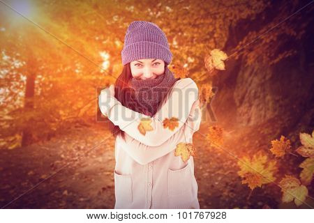 Attractive brunette looking at camera wearing warm clothes against autumn scene