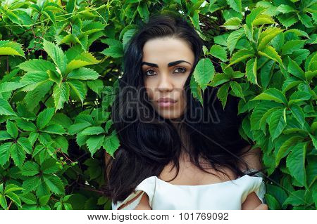 brunette in green leaves