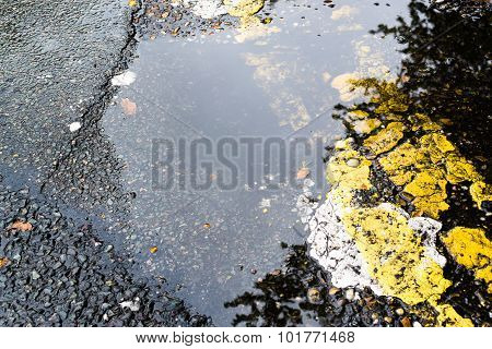 Broken Asphalt With A Rain Puddle