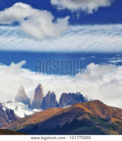 Three rocks Torres are surrounded by picturesque clouds. Fabulous harmony of the national park Torres del Paine in Chile