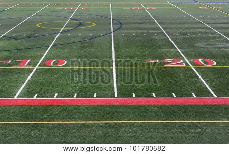 Closeup of the yardage markers on a football field. The numbers are in red on an artificial turf field.