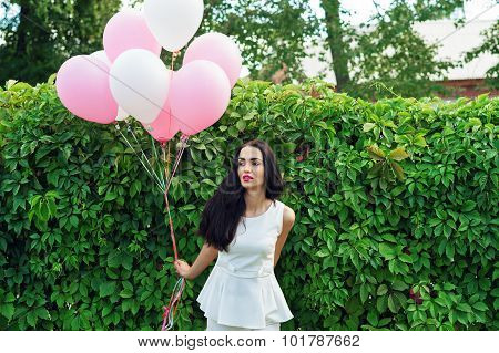 attractive brunette with balloons near the green hedgerow