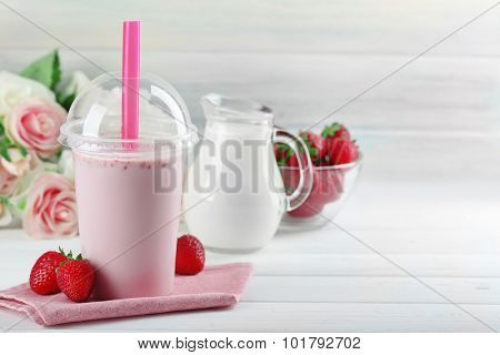 Plastic cup of milkshake on light wooden background