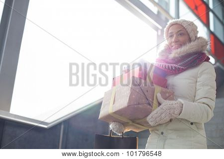 Smiling woman in warm clothing carrying stacked gifts by window