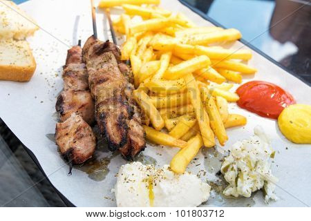 Souvlaki portion with french fries served on a table in a restaurant