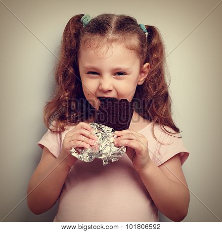 Cunning Kid Girl Eating Dark Chocolate With Pleasure And Curious Look
