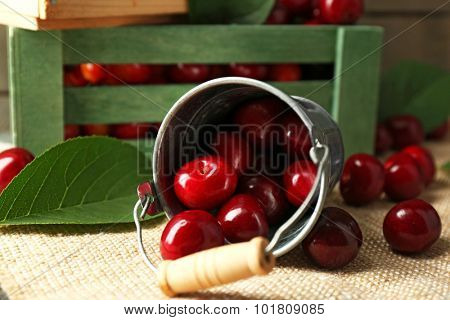 Sweet cherries with green leaves in bucket and wooden boxes, on wooden background
