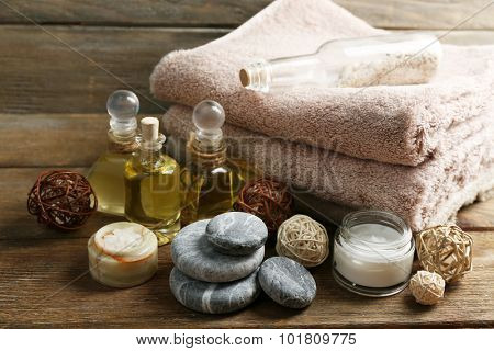 Stack of spa stones and spa treatments on wooden background