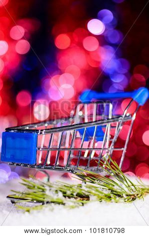 shopping cart on snow against blurred lights on christmas tree