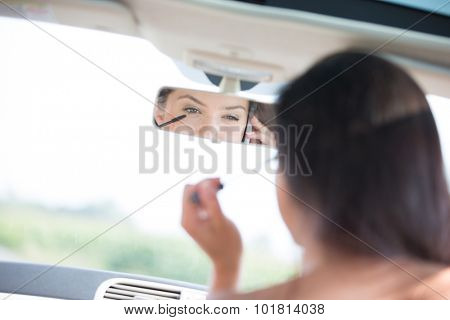 Reflection of woman using cell phone while applying mascara in rearview mirror of car