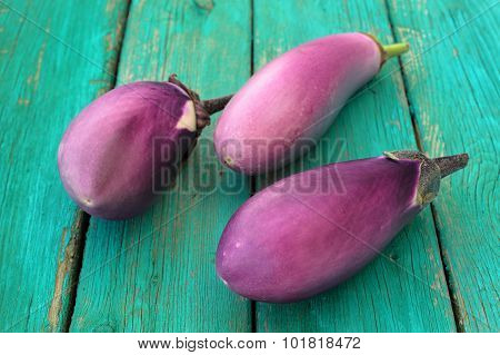 Three Whole Fresh Organic Violet Aubergines On Old Turquoise Table