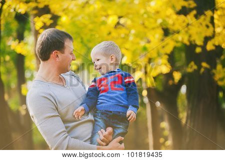 Happy Family Laughing And Playing In Autumn Wood