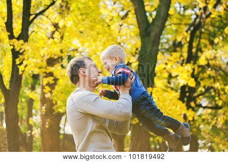 Happy Family Of Two People Laughing And Playing In Autumn Wood