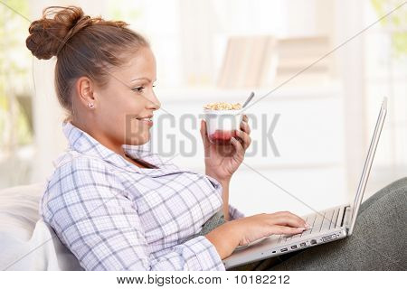 Young Woman Browsing Internet In Bed Smiling